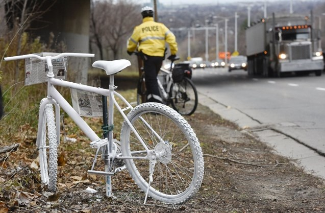 A Hamilton police officer leaves the scene where a ghost bicycle was placed as a memorial to Jay Keddy, who was killed riding his bike on the Claremont Access in December 2015.