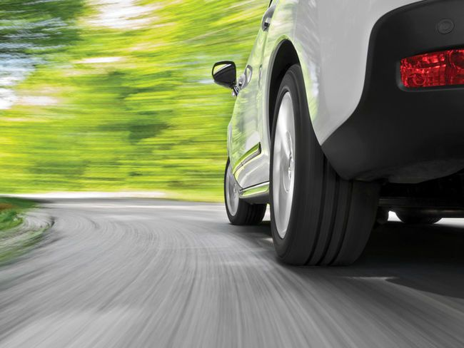 A stylised low-angle shot of a vehicle's wheels as the vehicle drives along a winding road.
